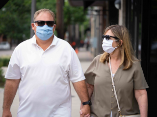 Happy couple wearing fabric face masks